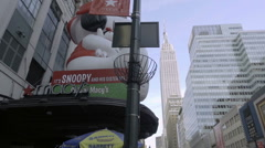 Big Snoopy balloon Macy's on 34th st with Empire State Building tilting down NYC Stock Footage