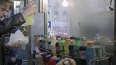Young man takes bottle of soda, purchasing drink from street cart food vendor Stock Footage