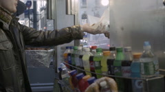 Young man takes hot dog from street cart food vendor with soda bottles lined up Stock Footage