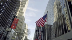 Rotating shot panning across American flags under tall towering skyscraper NYC Stock Footage