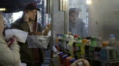 Woman taking bite of hot dog, man talking cell phone - slow motion street vendor Stock Footage