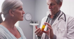 A senior doctor prescribing medication to an elderly patient - stock footage