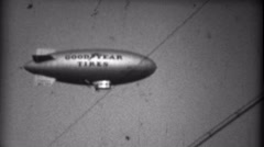 1935: Goodyear Tires blimp spotted flying over a sporting event. MIAMI, FLORIDA Stock Footage