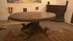 Round wood table and animal trophies at Corvin Castle, Hunedoara Stock Footage