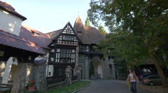 Walking under an arch gate near the Peles Castle Stock Footage