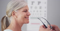 Mature woman receiving eyeglasses from optometrist - stock footage