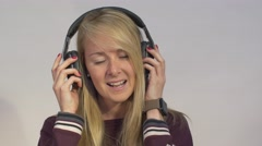 young blonde woman lifts headphone away from ear to hear someone talking - stock footage