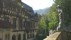 Statue next to the beautiful facade of Peles Castle - stock footage