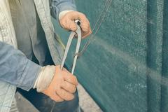 Tightening wire using a pincers - stock photo