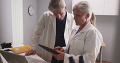 Two caucasian medical specialists talking in a lab - stock footage