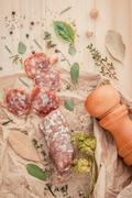 Sliced sausage salami with herbs and spices ,thyme, rosemary, saffron,basil, - stock photo