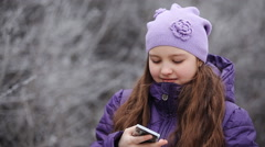 The girl in a winter fur cap speaks by phone outdoor Stock Footage