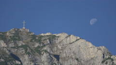 Heroes' Cross on the Caraiman Peak and the moon seen from Peles Castle Stock Footage