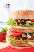 Sesame seed bun sandwich with beef patty, parma ham and cheese - stock photo