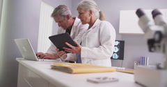 Two mature doctors working in a clinic - stock footage