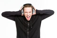 Man listening music in headphones and screaming - stock photo