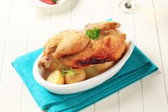 Roast chicken and new potatoes in a casserole dish Stock Photos