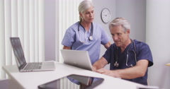 Two caucasian mature medical practitioners wearing scrubs - stock footage