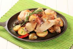 Chicken drumsticks and potatoes on a cast iron skillet - stock photo