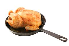 Roasted chicken on an iron skillet - stock photo