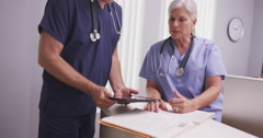 Mature female medical practitioner talking to male colleague at clinic desk Stock Footage