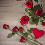 Red rose on old wood background (top view) - stock photo