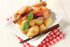 Roast chicken and new potatoes - still life - stock photo