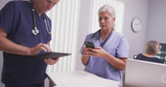 Mature male and female medical practitioners looking at tablet computer and cell - stock footage