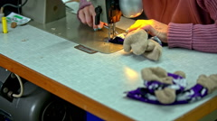 Sewing together plush body parts - stock footage