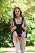 Happy mother walking with infant in baby carrier Stock Photos