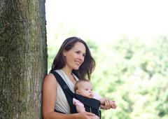 Mother smiling with infant in baby carrier - stock photo
