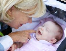 Smiling grandmother tickling baby - stock photo