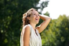 Carefree woman smiling with hand in hair outdoors - stock photo