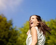 Carefree woman laughing outdoors - stock photo