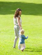 Mother and baby girl walking on grass - stock photo