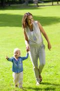 Mother and baby daughter walking outdoors Stock Photos