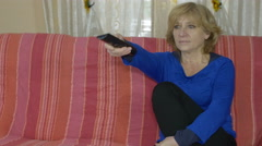 Blonde woman watching TV alone in her living room: switching with remote control Stock Footage