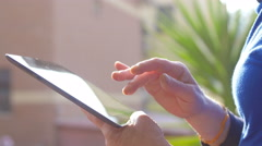 Hands of woman texting on the touchscreen of a tablet: natural lighting  Stock Footage