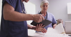 Senior female medical doctor or nurse reading patient file with male colleague Stock Footage