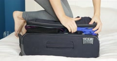 Young woman standing on her knees on overfilled suitcase, trying to close it Stock Footage