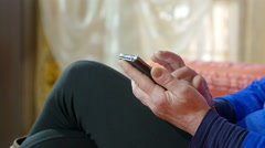 relaxed woman sitting on the sofa texting on the smartphone , mobile, cellphone  - stock footage