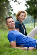 Portrait of a couple smiling and sitting on grass outdoors - stock photo