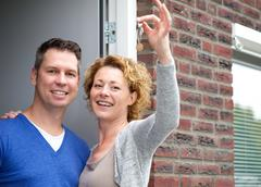 Happy couple holding keys to their new home - stock photo