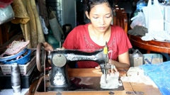 Asian woman sews on the old sewing machine Stock Footage