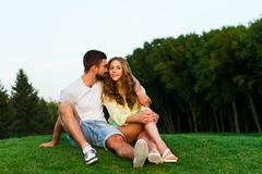 Stock Photo of Guy and girl hugging in the park. Evening date.
