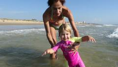 Baby and mom playing with waves Stock Footage