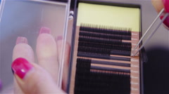 Picking black eyelash extensions from box close up 4K - stock footage