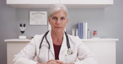 Smilling attractive mature female doctor talking to camera patient POV - stock footage