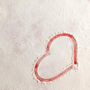 Valentine love red heart shape in snow on red background. Stock Photos