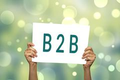 B2B (marketing) card in hand with abstract light background. Kuvituskuvat